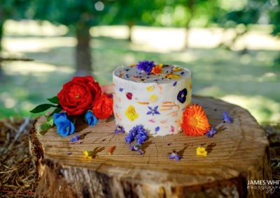 Buttercream wedding cake with edible flowers on log cake stand